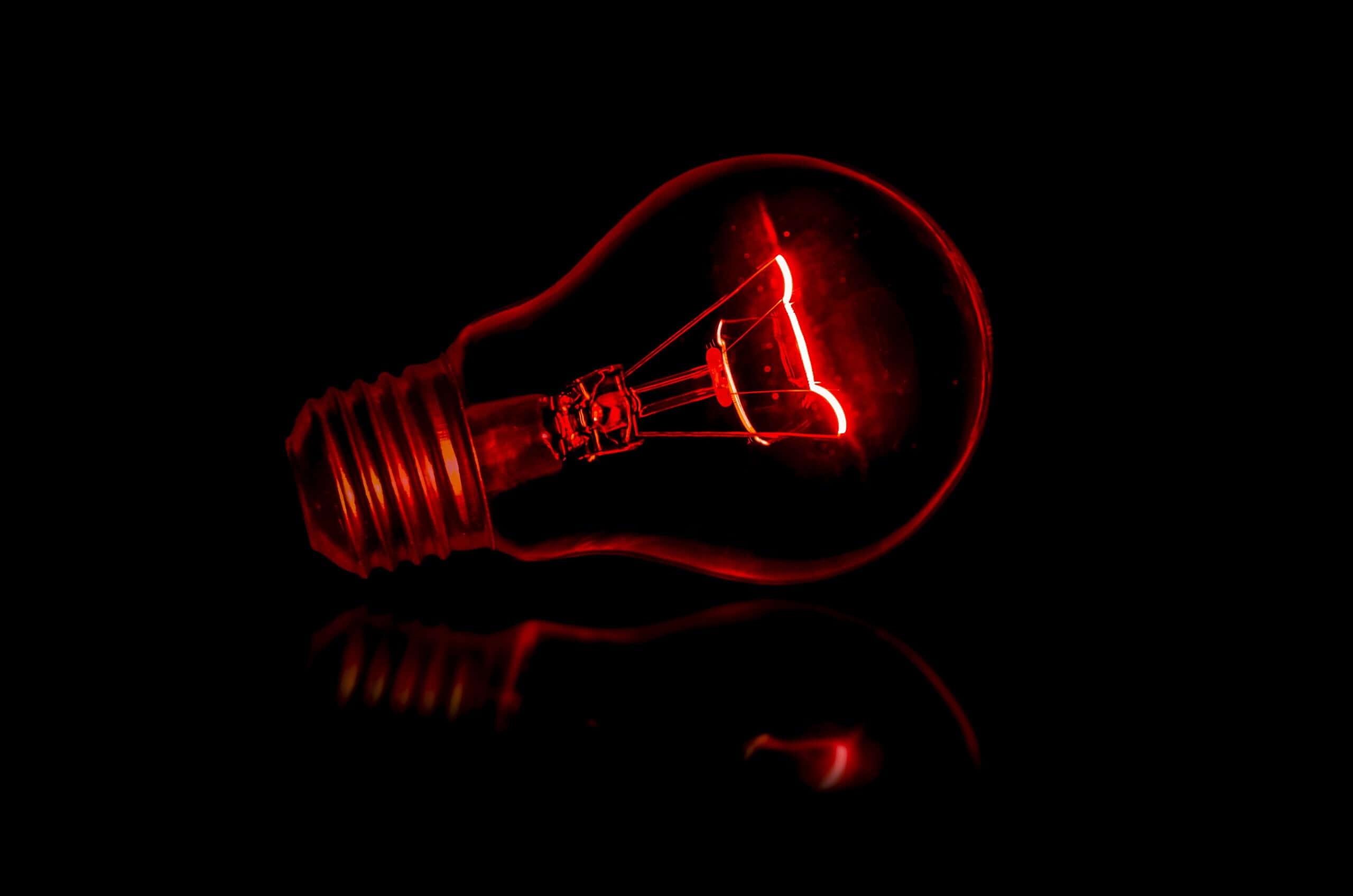 red lightbulb on black background
